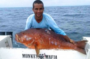 Photo of Chimpi Mataritta holding a large orange fish.