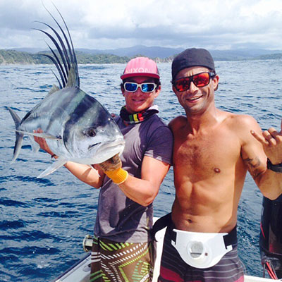 Captain Chimpy and his mate Marco smile with their Rooster fish on board the Cowboy 38, during a private charter tour off the coast of Nosara, Costa Rica.